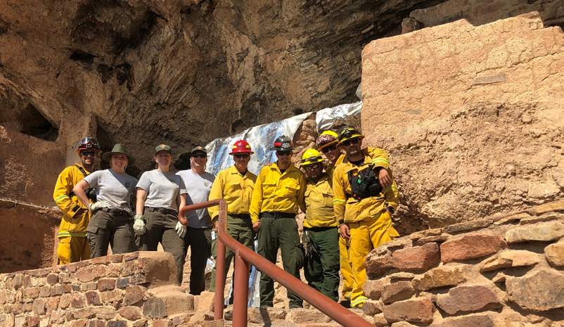 Crew in front of wrapped cliff dwelling
