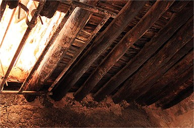 Wooden ceiling of a room in the Lower Cliff Dwelling with opening to next floor.