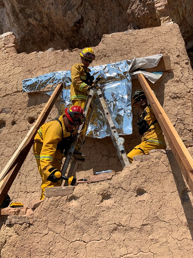 Crew wrapping modern wood in cliff dwelling