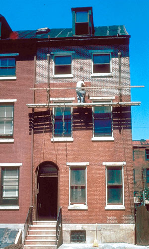 Worker on scaffold repointing a brick building.