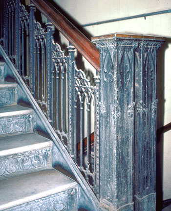 Cast iron newel post and decorative stair railing.