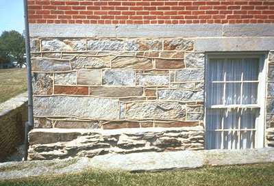 Stone foundation below a brick wall
