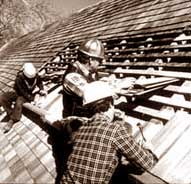 Three Men Working On A Shingle Roof.