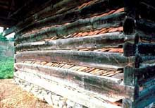Chinking areas between logs filled with stones and wood strips.