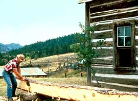 Man using a broad axe to hew logs in front of a log building.