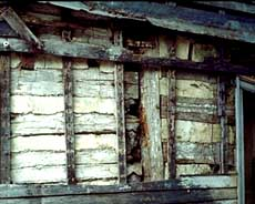 Portion of a log structure with missing siding and exposed logs.