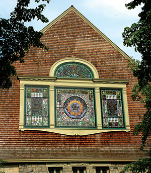 Gable End Of A Church Covered With Wood Shingles And Stained Glass Tripartite Window