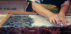 Womenu0027s Hands Cleaning Stained Glass On A Table.