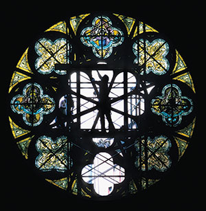 Person Repairing A Round Stained Gl Window Silhouetted In The Middle Of