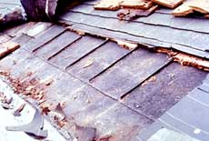 Section of a standing seam metal roof, with remains of a shingle roof above it.