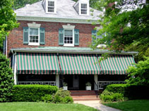 Green And Burgundy Awnings On The Porch Of A Two Story Red Brick House With