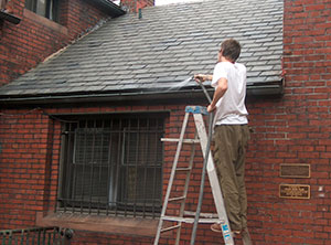 Man on a ladder using a hose to clean out gutters on a brick building with a slate roof. Photo: Bryan Blundell.