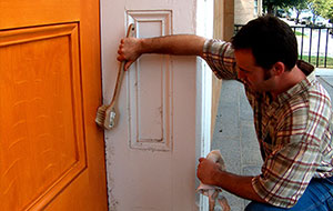 Man using a brush to remove debris from a paneled wood door and door surround.