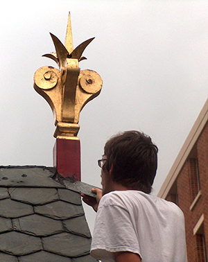 Man looking at a decorative wood element projecting upward from a slate roof. Photo: Bryan Blundell.