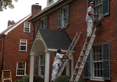 Two men on ladders painting woodwork on the exterior of a brick house.