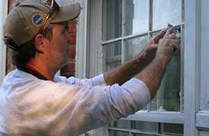Man using a tool to repair a window.