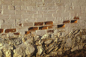 Close-up of a painted brick wall with some spalled bricks. Photo: NPS files