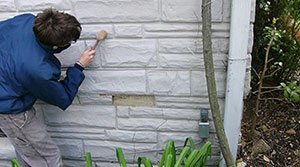 Man Using A Wooden Mallet To Test The Stucco On The Foundation Of A  Building. Stucco Applied To An Exterior Wall ...
