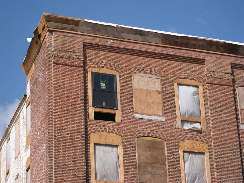 Red Brick Building With Boarded Up Windows And Window Openings That Have Been Blocked Down