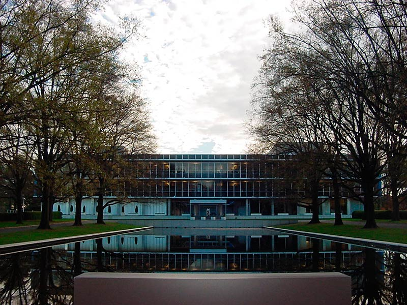 Trees Flanking A Pool Of Water In Front Of An International Style Office  Building.