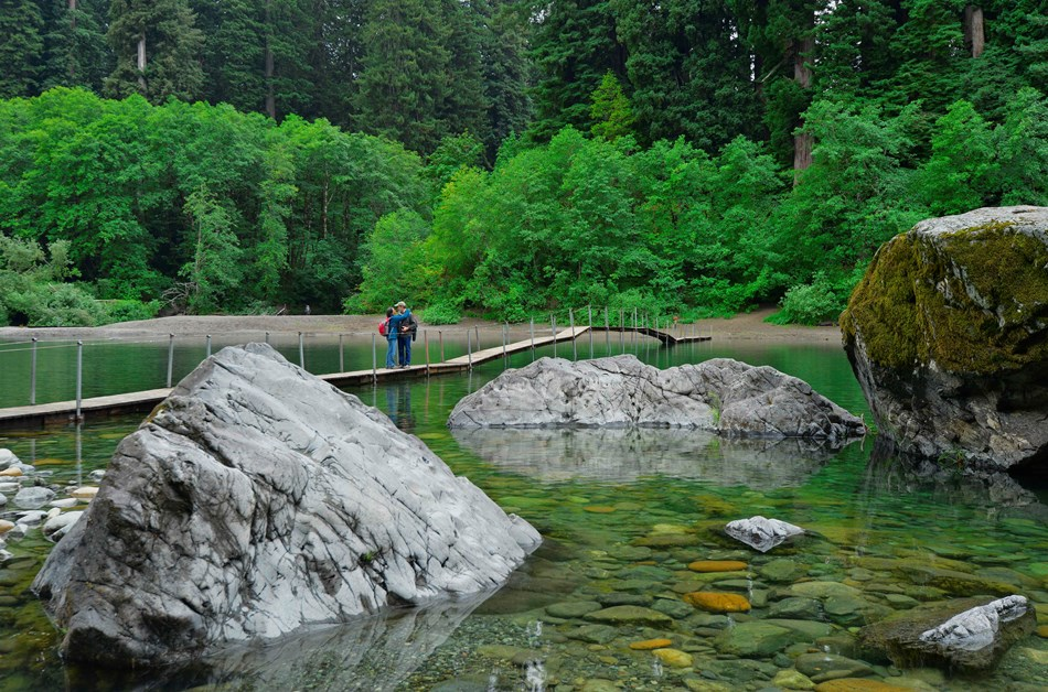 Two adults stand on a wooden hiker's bridge over a clear river. Redwoods line the riverbank.