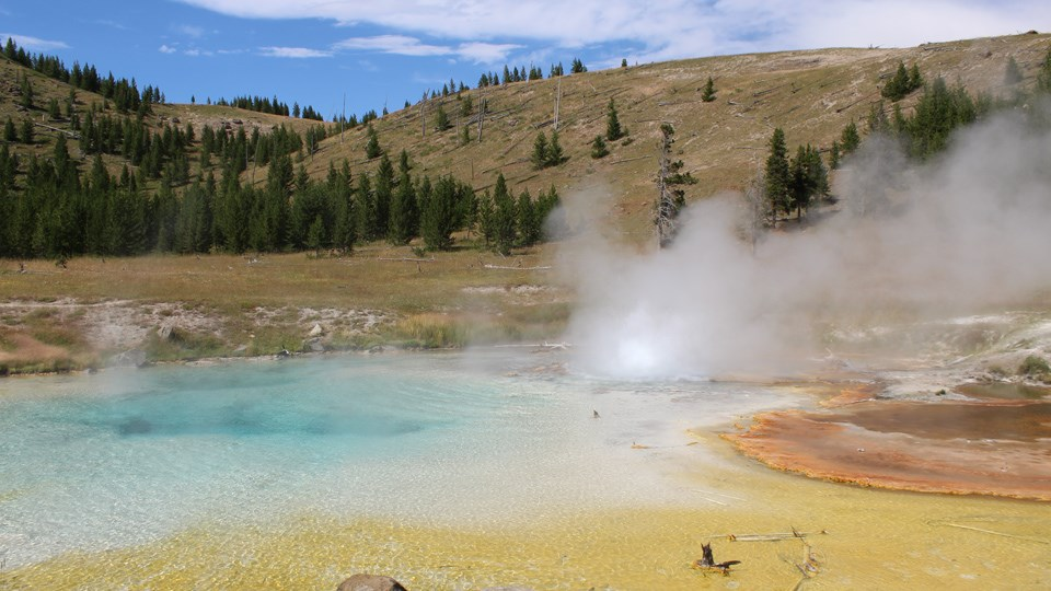 Vivid blues and oranges in a steamy hot spring along the trail.
