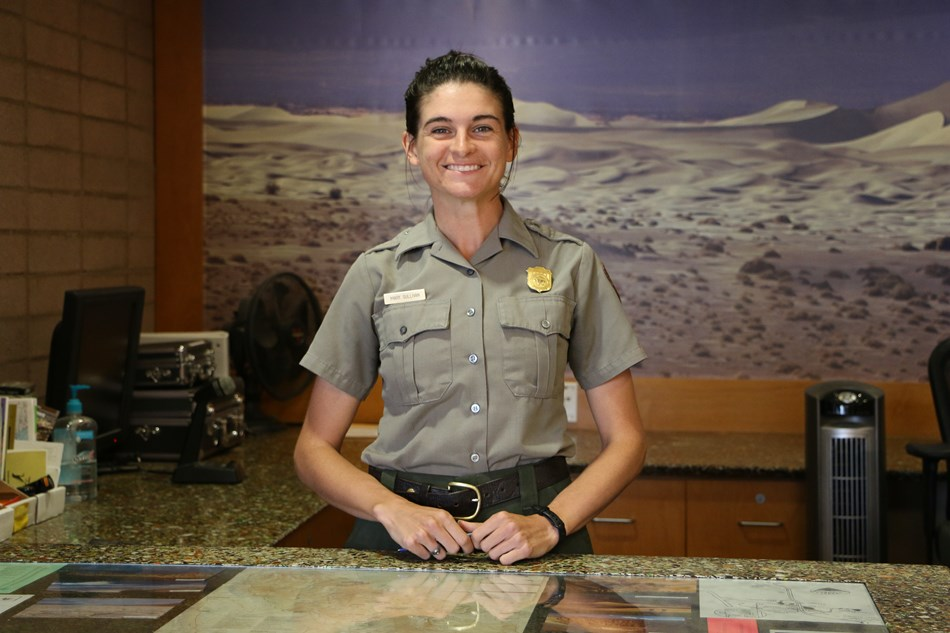A women in a park ranger uniform stands behind a desk.
