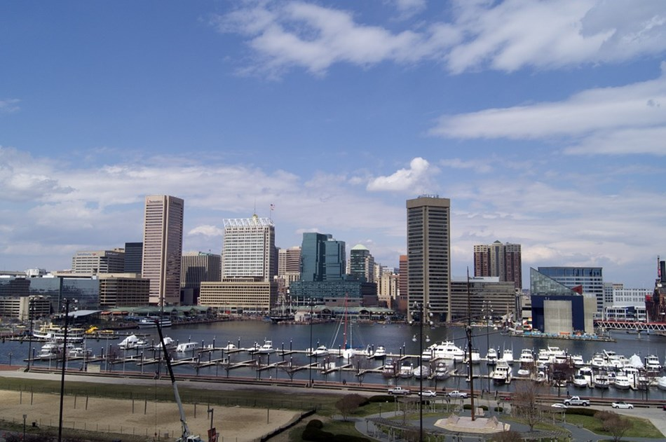 Photograph of Baltimore with water and boats in foreground and buildings in background.