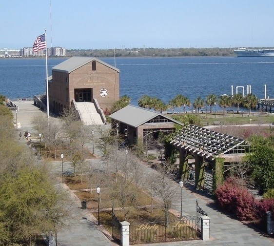 Photograph of the Fort Sumter Visitor Center at Liberty Square, the primary departure point for the boat ride to Fort Sumter. Visitor Center in the foreground with harbor in the background.