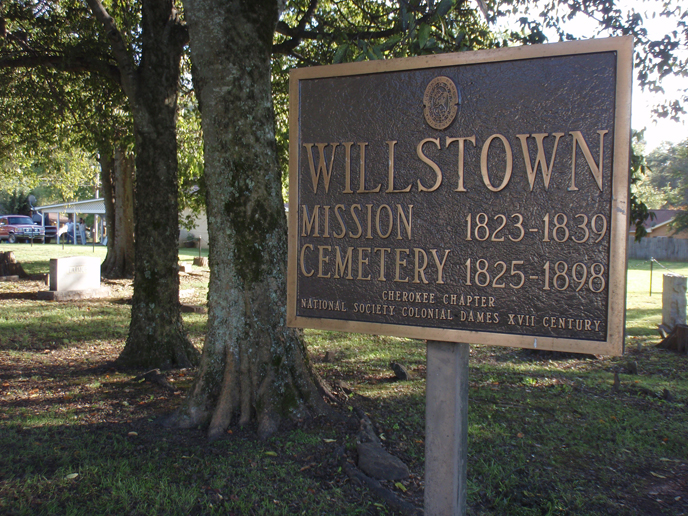 metal sign that says Willstown Mission Cemetery, trees in background