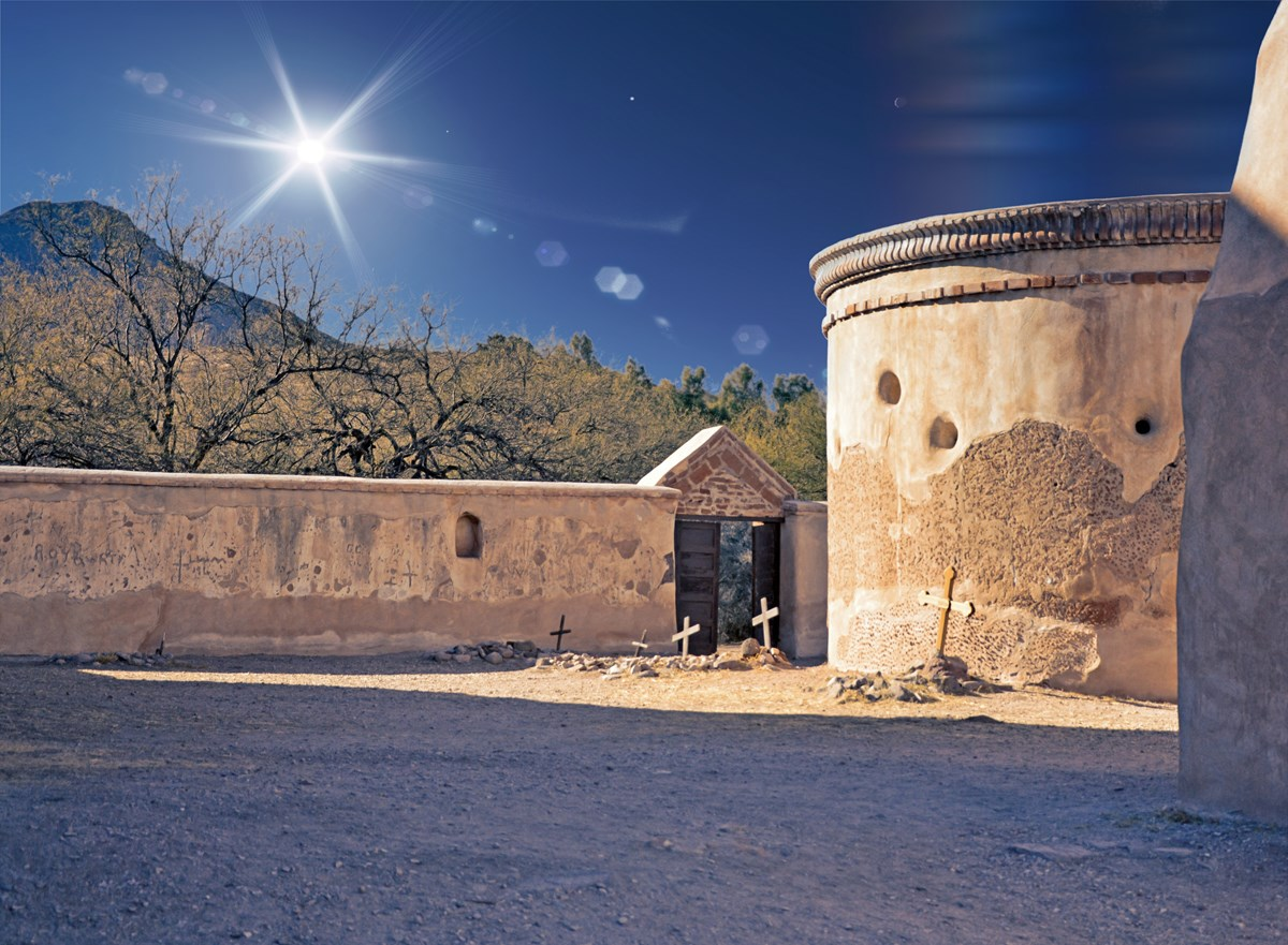 Photograph of adobe mortuary chapel with light from sun all around.