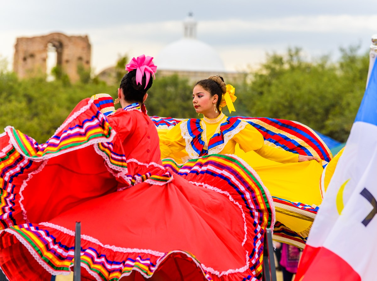 Dancers in colorful outfits dancing with church in background.