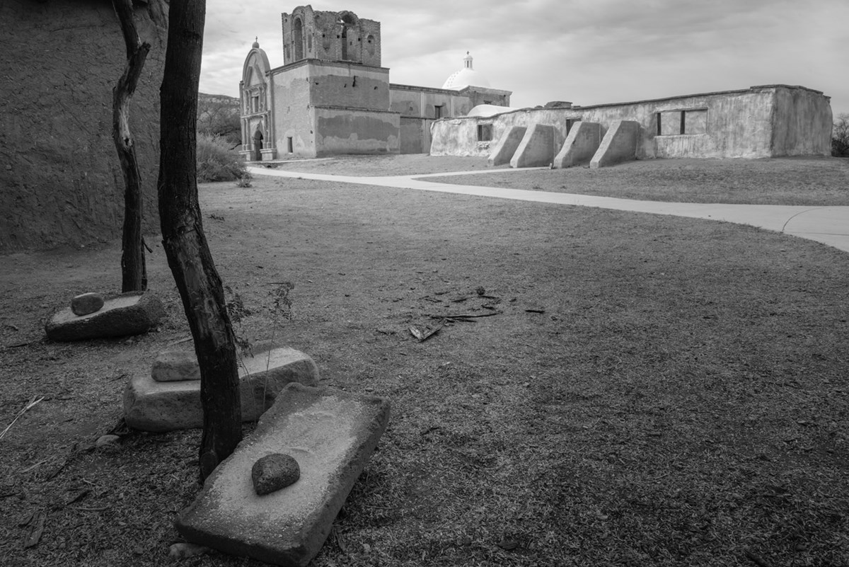 Black and white photograph of grinding stones on the ground with adobe church in background.