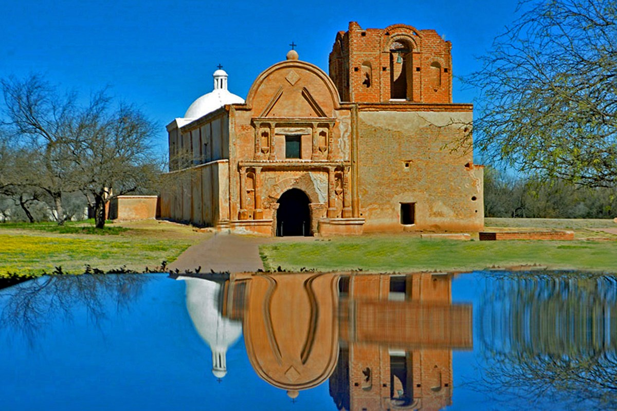 Photograph of reflection of adobe church with church in background.