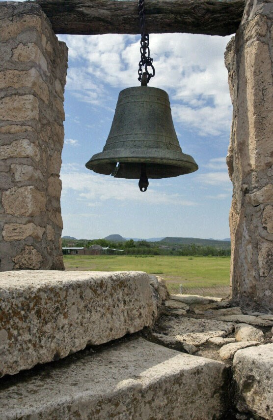 bell in stone tower with landscape behind