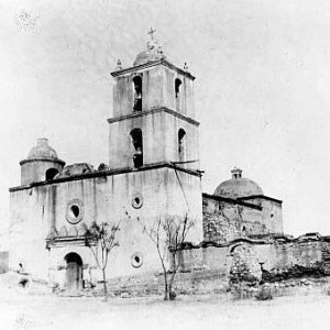 black and white historic photo of mission church with 4-story large bell tower
