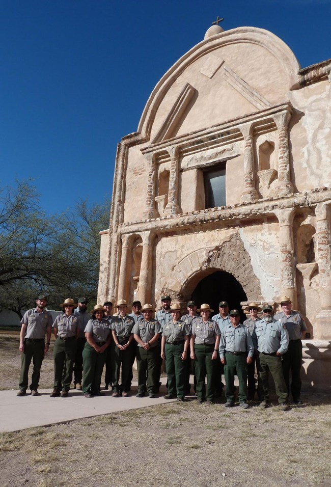 uniformed ranger staff standing in front of adobe mission church