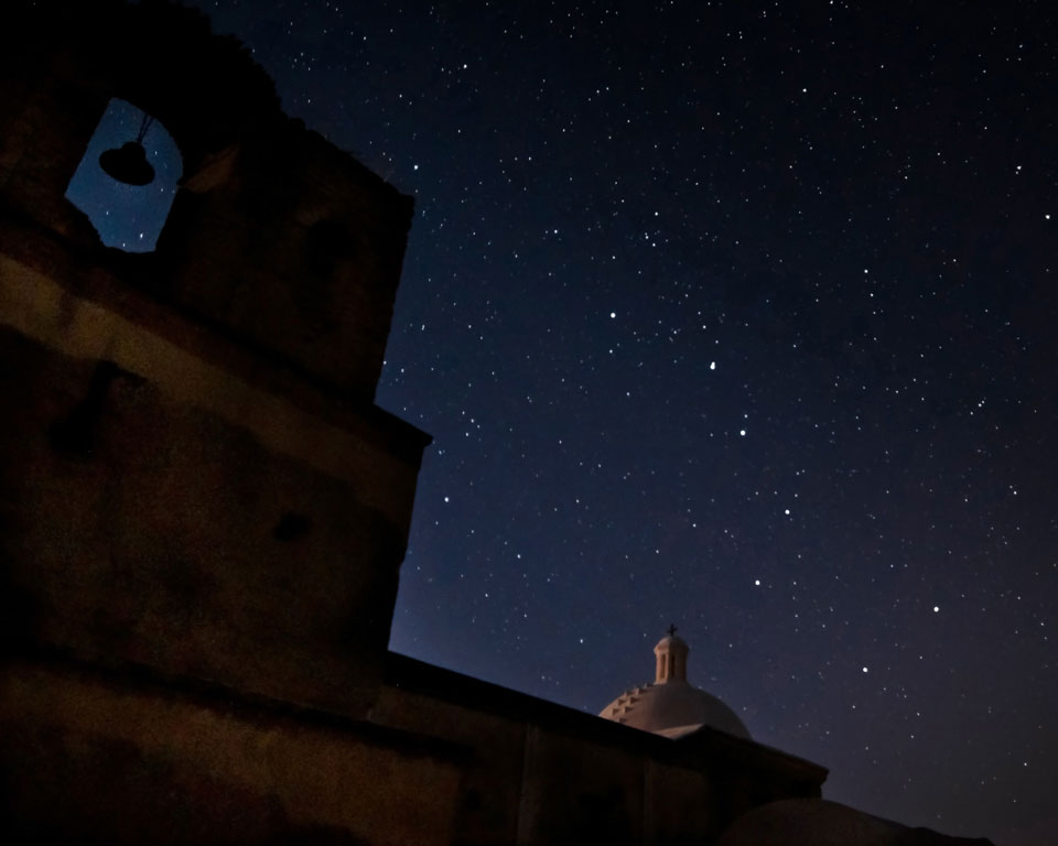 stars in night sky above church dome and bell tower