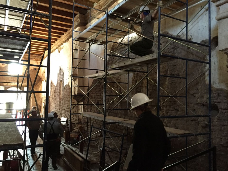 scaffolding and workers inside adobe church