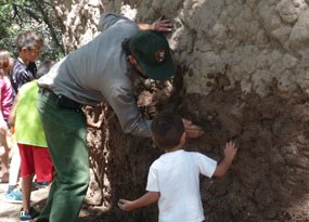 ranger and children applying mud to side of mud structure