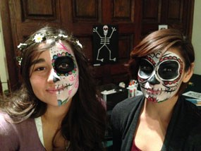 two young women with faces painted as skeletons