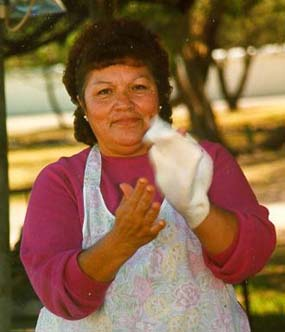 woman stretches masa between her hands for flour tortilla