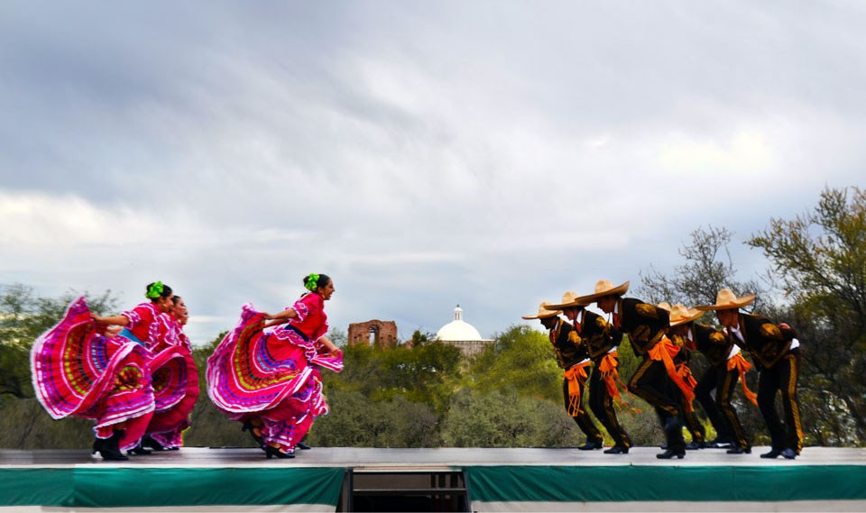 folklorico dancers on stage, men on right, women on left, church dome and trees in the middle, gray sky above