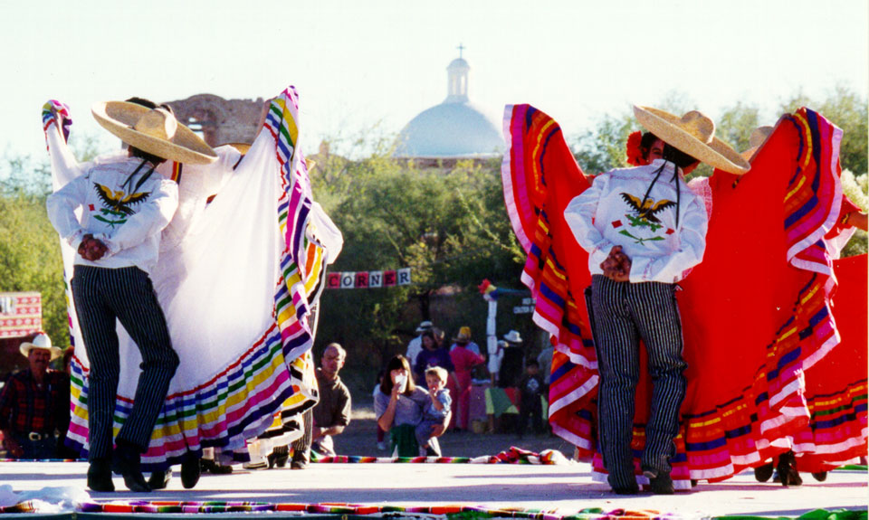 folklorico dancers on stage in front of church dome