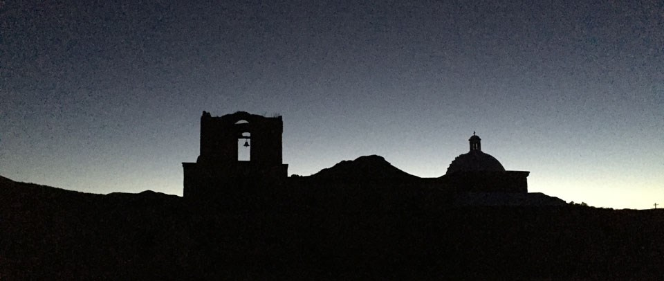 silouette of bell tower, dome, and mountain against night sky
