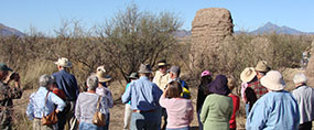 group of people standing in front of adobe ruin