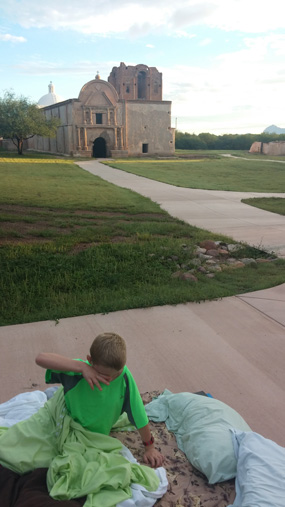 boy rubbing eyes in early morning with church in background