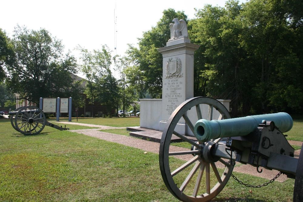 Tupelo National Battlefield Site cannon in foreground, monument, and cannon and interpretive sign in background