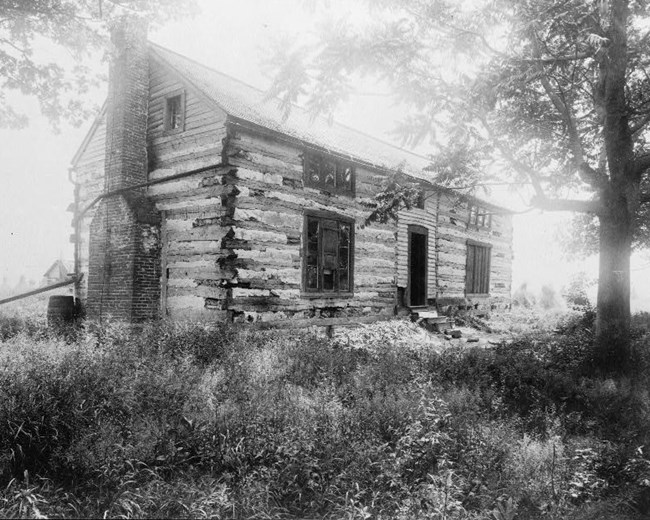 Black and white photograph of a two-story log cabin.