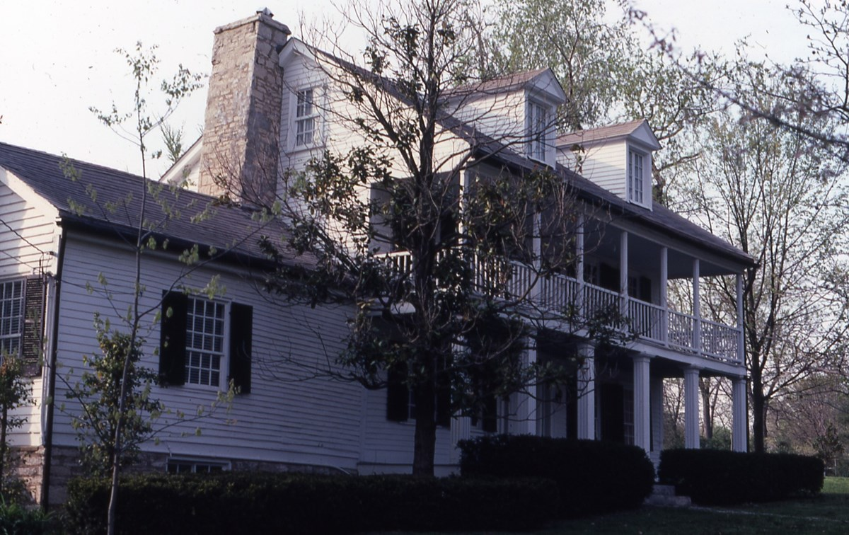 Color photograph of a white 19th century frame house with columns and dormers
